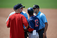 Lowell Spinners coach Nate Spears (left) and manager Corey Wimberly (13) talk with umpires Dylan Bradley (left) and Thomas Fornarola (right) after Spears was ejected during a game against the Batavia Muckdogs on July 15, 2018 at Dwyer Stadium in Batavia, New York.  Lowell defeated Batavia 6-2.  (Mike Janes/Four Seam Images)