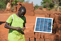 MALAWI, farmer charges his mobile phone with solar panel in village / MALAWI, Bauer Charles Zimba laedt seine Batterie fuer das Mobiltelefon mit einem Solar Panel