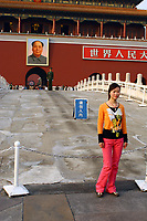 CHINA. Beijing.  A woman stands in front of the famous Mao Zedong portrait that hangs on the 'Gate of Heavenly Peace' which leads into the Forbidden City and is opposite Tiananmen Square. Mao is still revered in China even 30 years after his death and 40 years since the end of the 'Cultural Revolution' and the 'Great Leap Forward' where it is alleged he was responsible for the death of some 20 million Chinese people. Nevertheless, every day thousands of Chinese people make the pilgrimage to stand and have their photo taken in front of his most famous portrait. 2005.