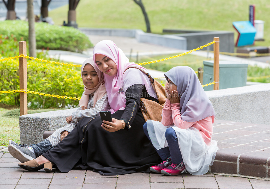 Mother Taking a Selfie of Herself and Daughter, KLCC Park, Kuala Lumpur, Malaysia.