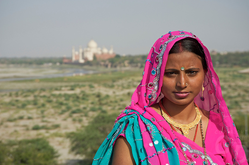 An Indian Bride at the Agra Fort visiting after the wedding, the Fort is a UNESCO World Heritage site located in Agra, India. The fort is also known as Lal Qila, Fort Rouge and Red Fort of Agra. It is about 2.5 km northwest of its much more famous sister monument, the Taj Mahal. The fort can be more accurately described as a walled palatial city...It is the most important fort in India. The great Mughals Babur, Humayun, Akbar, Jehangir, Shah Jahan and Aurangzeb lived here, and the country was governed from here. It contained the largest state treasury and mint. It was visited by foreign ambassadors, travellers and the highest dignitaries who participated in the making of history in India..