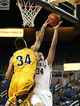 Northwest Christian's Jay Mayernik blocks a shot from Nevada's Lucas Stivrins during a college basketball game in Reno, Nev., on Sunday, Dec. 28, 2014. Nevada won 81-67.<br /> Photo by Cathleen Allison