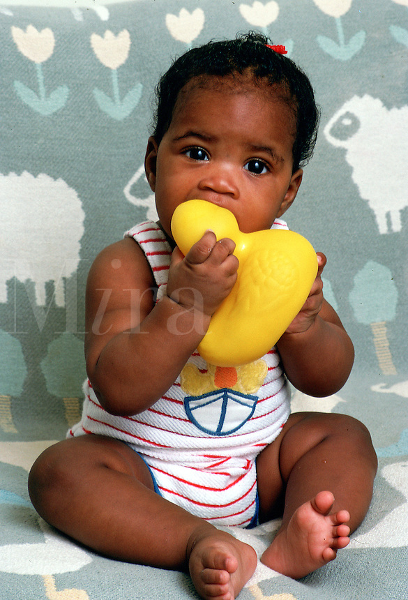 An infant girl sits while teething on a toy.