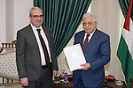 Palestinian president Mahmoud Abbas receives the annual report from a head of the Palestinian Monetary Authority, in the West Bank city of Ramallah on July 15, 2021. Photo by Thaer Ganaim
