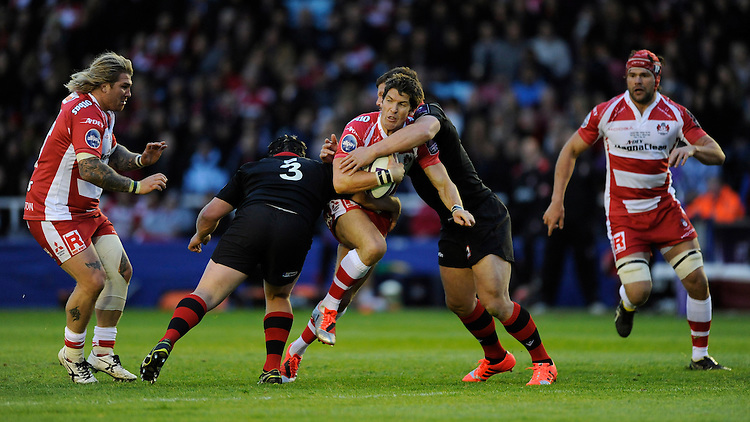 James Hook of Gloucester Rugby offloads to Richard Hibbard of Gloucester Rugby as he is tackled by WP Nel and Ross Ford of Edinburgh Rugby