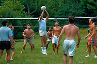 Group of adults playing outdoor volleyball.