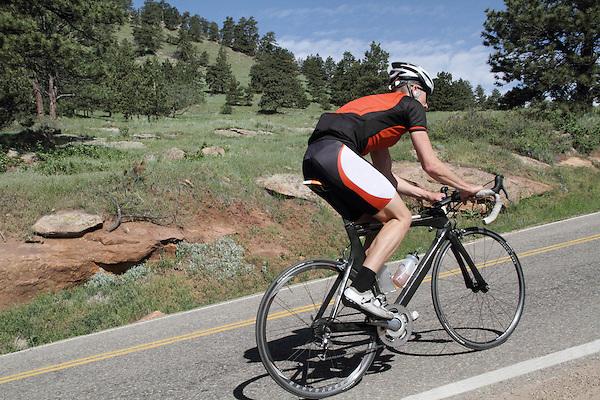 Senior citizen biking up Flagstaff Mountain Boulder, Colorado, USA. .  John offers private photo tours in Denver, Boulder and throughout Colorado. Year-round.