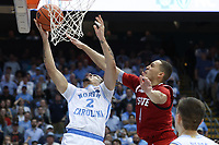 CHAPEL HILL, NC - FEBRUARY 25: Cole Anthony #2 of the University of North Carolina avoids a block attempt by Jericole Hellems #4 of North Carolina State University during a game between NC State and North Carolina at Dean E. Smith Center on February 25, 2020 in Chapel Hill, North Carolina.