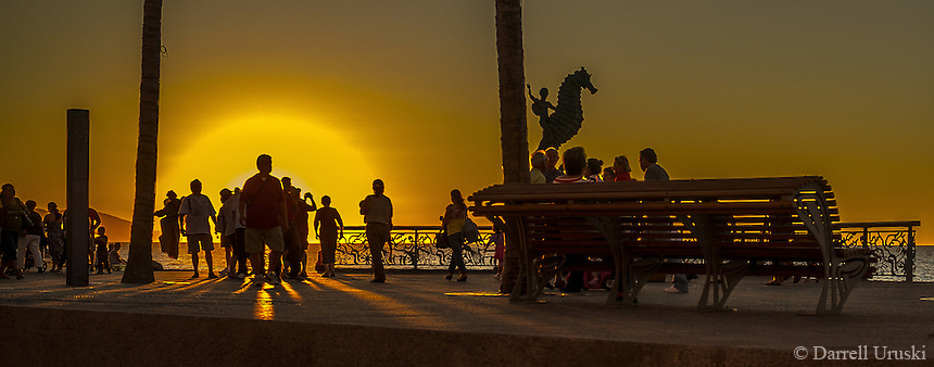 Fine Art Landscape Photograph of crowds gathering to photograph the setting sun on the Malecon, in Puerto Vallarta, Mexico.