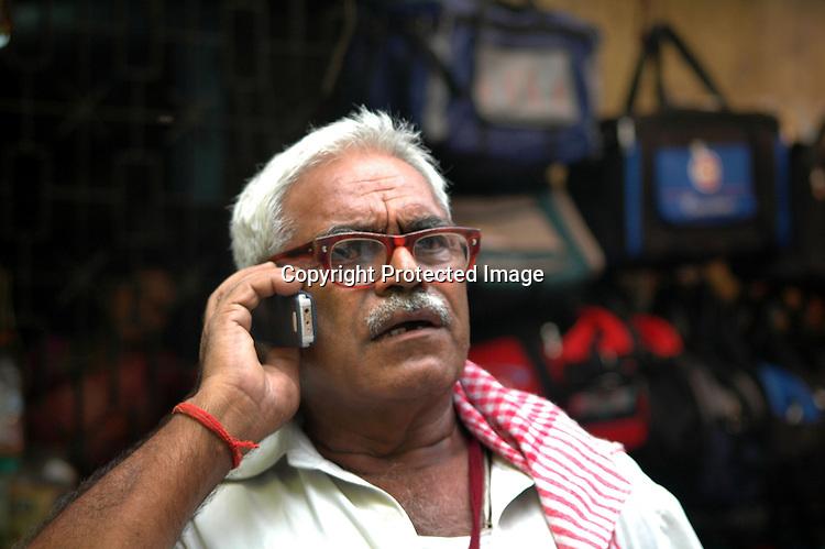An old Indian man using a mobile phone on a road of  Kolkata, West Bengal,  India   Arindam Mukherjee
