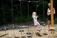 Amelia Cracraft, 3, of Rogers works on her balance as her mom Sarah Cracraft (right) looks on, Sunday, July 18, 2021 at the playground at Lake Atalanta. Check out nwaonline.com/210719Daily/ for today's photo gallery. <br /> (NWA Democrat-Gazette/Charlie Kaijo)