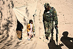 An Afghan soldier looks down at two girls standing in the doorway of their home as their father talks to U.S. and Canadian troops in the village of Ashoque in Zhari district, Kandahar province, Afghanistan. Dec. 2, 2009. DREW BROWN/STARS AND STRIPES