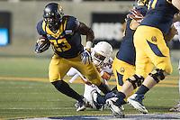 BERKELEY, CA - September 17, 2016: Cal running back (23) Vic Enwere breaks through the tackle of a Texas defender at Cal Memorial Stadium.