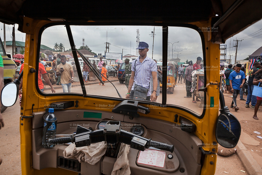 """Nigeria. Enugu State. Enugu. Town center. View on the road from a yellow auto rickshaw used by """"Keke"""" drivers for transporting people around town. The tricycle better known in Nigeria as the Keke NAPEP is gaining the dominance on Nigerian roads sweeping every street of cities and villages. The auto rickshaw is a common form of urban transport, both as a vehicle for hire and for private use. Side mirrors and plastic water bottle. Enugu is the capital of Enugu State, located in southeastern Nigeria. 28.06.19 © 2019 Didier Ruef"""