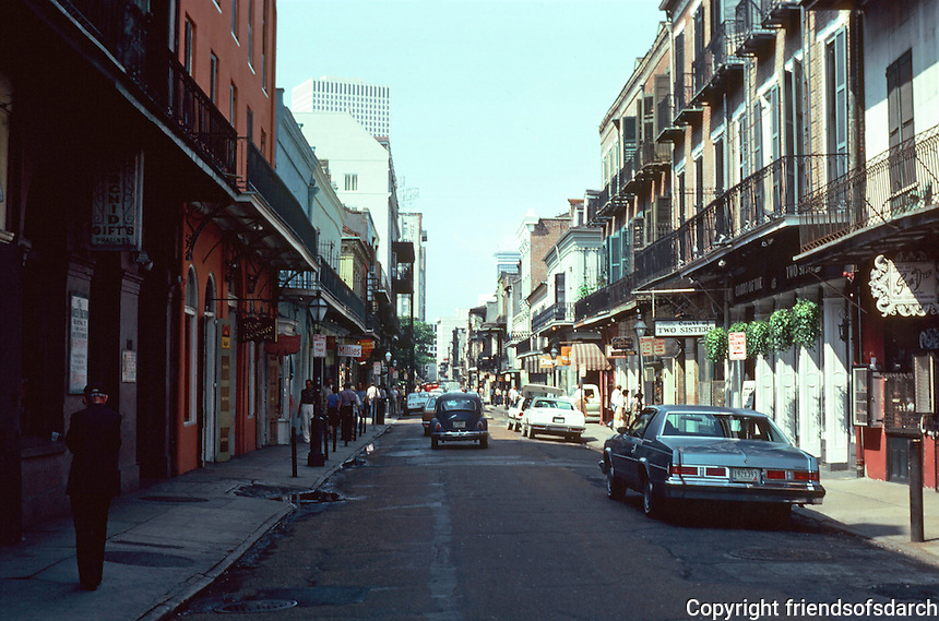 New Orleans:  View down Toulouse St. from Bourbon St.  Narrow street with buildings up against narrow side walks.  Storefronts with residential above.