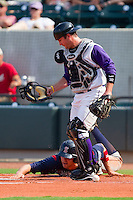 Catcher Logan Johnson #32 of the Winston-Salem Dash looks for the ball as Ryan Lavarnway #33 of the Salem Red Sox dives back to touch home plate at  BB&T Ballpark June 27, 2010, in Winston-Salem, North Carolina.  Photo by Brian Westerholt / Four Seam Images