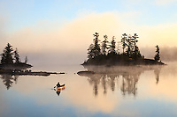 """""""Paddling to Sunrise""""<br /> The canoeist paddles toward the foggy sunrise in the Boundary Waters Canoe Area Wilderness (BWCAW). The wilderness provides an abundance of solitude and serenity for the soul. <br /> <br /> This photograph is from our Canoescapes Series. This photograph was also honored as a finalist in the 12th annual Smithsonian.com photo contest. Of 26,500 entries from photographers in 93 countries, it was one of 10 finalists in the Americana category in 2014."""