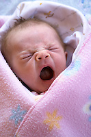 Infant girl yawning in pink planket