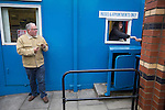 Ramsbottom United 1 Barwell 3, 03/10/2015. Riverside Stadium, Northern Premier League. A spectator paying in to the Harry Williams Riverside Stadium, home to Ramsbottom United before they played Barwell in a Northern Premier League premier division match. This was the club's 13th league game of the season and they were still to record their first victory following a 3-1 defeat, watched by a crowd of 176. Rams bottom United were formed by Harry Williams, the current chairman, in 1966 and progressed from local amateur football  in Bury to the semi-professional leagues. Photo by Colin McPherson.