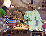 """A woman sells """"masas"""" (flour pancakes served with spices) to travelers in Fada N'Gourma on the road connecting Burkina Faso with neighboring Niger."""