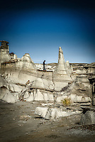 A lone figure stands amidst the spires and hoodoos of the Bisti Wilderness in New Mexico's San Juan Basin