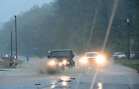 Motorists navigate flood water and debris during heavy rain on Wednesday April 28 2021 along Arkansas 12 in the Prairie Creek community east of Rogers. Go to nwaonline.com/210429Daily/ to see more photos.<br />