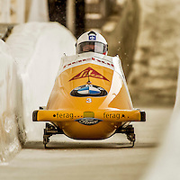 8 January 2016: Rico Peter, piloting his 2-man bobsled for Switzerland, enters the Chicane straightaway on his first run, ending the day with a combined 2-run time of 1:51.46 and earning a 9th place finish at the BMW IBSF World Cup Championships at the Olympic Sports Track in Lake Placid, New York, USA. Mandatory Credit: Ed Wolfstein Photo *** RAW (NEF) Image File Available ***
