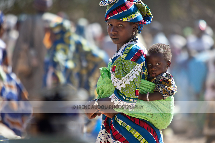 In the village market of Bourro in northern Burkina Faso, a Fulani woman carries her son on her back in traditional African fashion.  The Fulani are traditionally nomadic pastoralists, crisscrossing the Sahel season after season in search of fresh water and green pastures for their cattle and other livestock.