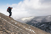 Hiker descending open ledge on the summit of Mount Crawford in Hadley's Purchase, New Hampshire USA.