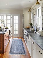 The stylish kitchen has painted wood panelling on the walls and a wood floor. The white units are topped by grey granite counter tops.