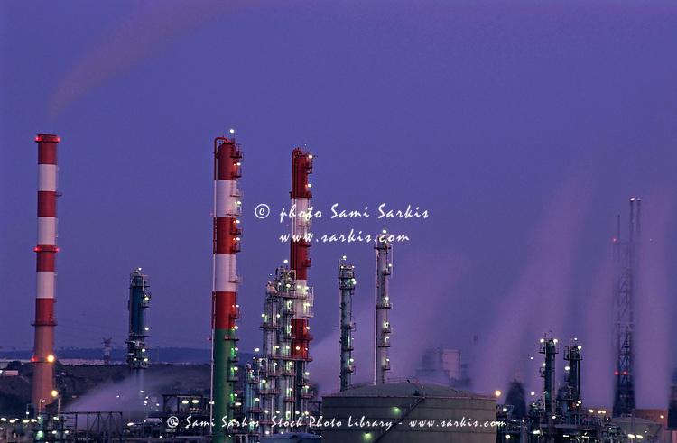 Petroleum refinery chimneys at dusk, France.