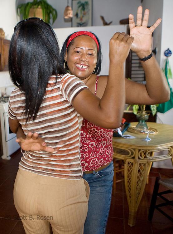 Villa Carolisol's maids dance bachata in the kitchen.