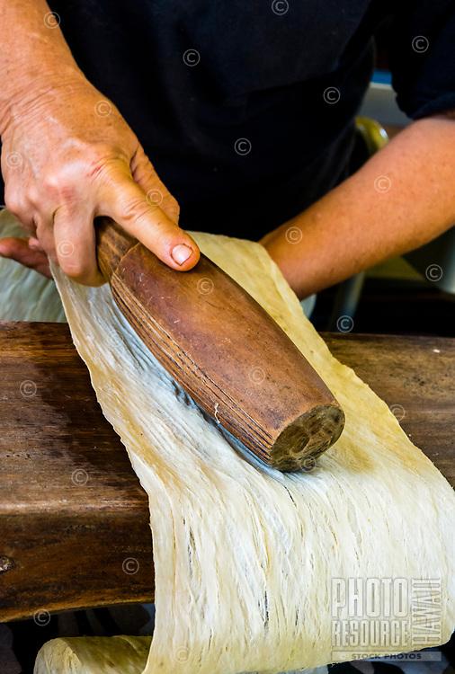 Kapa making on the Big Island: A kapa-making artist beats a wauke (paper mulberry) bast with a hobos (round wooden beater).