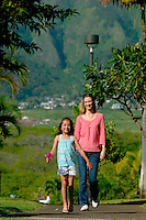 Mother and daughter walking pathway in green neighborhood with mountains in background.