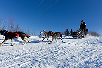 Dallas Seavey runs down the bank to the Innoko river as she leaves the Shageluk village checkpoint during the 2011 Iditarod race.