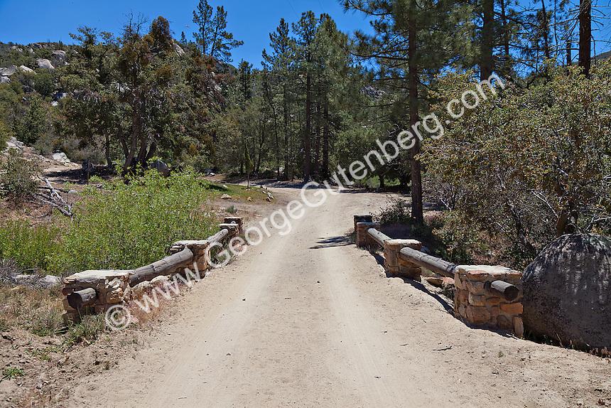 Rustic ranch road leads across bridge