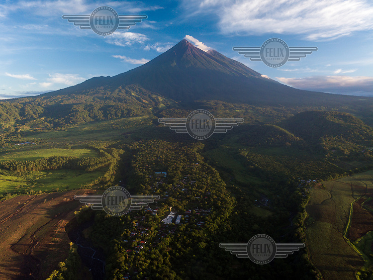 North-facing landscape of the community of La Trinidad that shows how it is surrounded by three volcanic debris causeways as well as the Fuego and Acatenango volcanoes in the background. The community's coffee, corn and bean fields are located closer to the volcano. The 3 June 2018, eruption destroyed roughly 70% of the community's arable land.