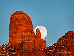 Wolf Moon Rising over Mitten Ridge, Sedona.  The nearly full Wolf (January) Moon poses with Mitten Ridge, whose red sandstone formations loom over Sedona, Arizona.  The patches of snow are remnants from a winter snowstorm that passed through the area in the preceding days, leaving some much needed moisture in our drought-stricken state.<br /> <br /> Image ©2021 James D. Peterson