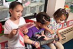 """Education preschool 4-5 year olds pretend play three girls playing together singing song from class songbook and """"playing"""" guitar horizontal"""