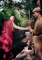 The Dalai Lama blessing guard with rifle in Dharamsala, India 1997