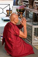 Myanmar, Burma, Yangon.  Sule Pagoda.  Buddhist Monk Performing Early-Morning Prayers.
