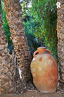 Clay jar by Palm tree trunks in garden, Tunisia (Licence this image exclusively with Getty: http://www.gettyimages.com/detail/110048321 )