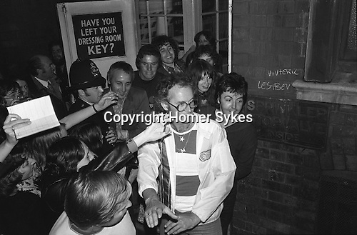 """Paul and Linda McCartney Wings Tour 1975.   Paul leaves by the stage door, after the Liverpool performance. Fans clamour to catch a glimpse of him. Bel Bush the promoter holds back fans. England. Brian Brolly managing Director of MPL under the word """"key"""" The photographs from this set were taken in 1975. I was on tour with them for a children's """"Fact Book"""". This book was called, The Facts about a Pop Group Featuring Wings. Introduced by Paul McCartney, published by G.Whizzard. They had recently recorded albums, Wildlife, Red Rose Speedway, Band on the Run and Venus and Mars. I believe it was the English leg of Wings Over the World tour. But as I recall they were promoting,  Band on the Run and Venus and Mars in particular."""