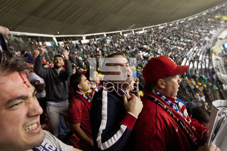 USA fan watch out for objects thrown by Mexican fans at the American supporters section protected by Mexican police at Azteca stadium before the USA vs. Mexico World Cup Qualifier in Mexico City, Mexico on March 26, 2013.  The man in the lower left hand of the image was bleeding after being hit by a flying object.