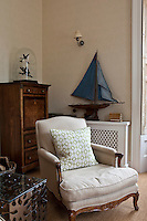An armchair upholstered in neutral fabric stands in the corner of a room in front of an antique chest of drawers.