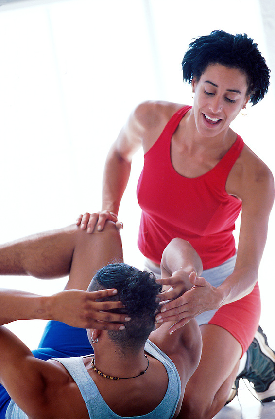 Woman acts as personal trainer for man during his workout.