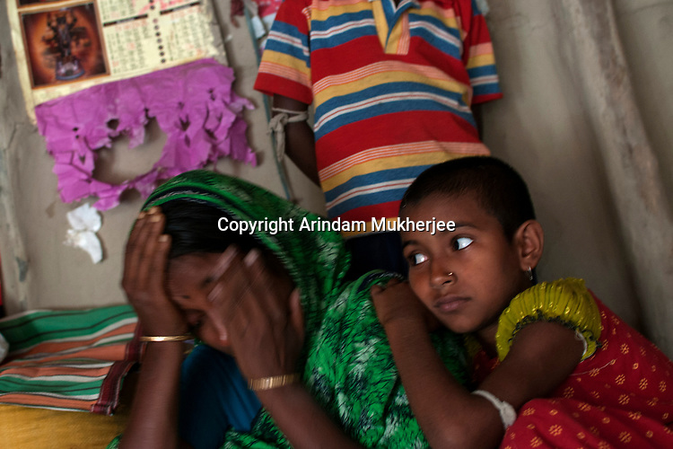 Rita Mandal, 31, with her children mourns in her house. She is the widow of late Srinath Mandal (32) who was killed by a tiger on 11th of April 2011. Sunderban, West Bangal, India. April 2011. Arindam Mukherjee