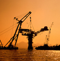 Crane barge lifting topside onto oil loading column for North Sea oil field. Scotland..