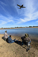 Anglers watch airplanes land while fishing for trout on Dec. 26 2020 at Lake Bentonville. The lake hugs the runway on the north side of the airport.<br />(NWA Democrat-Gazette/Flip Putthoff)