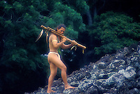 Hawaiian man with flute at Ulupo heiau, ancient temple site. Oahu